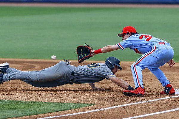 Missouri's Kameron Misner dives back to first base ahead of the throw to Ole Miss first baseman Kevin Graham during the first inning of the Southeastern Conference tournament NCAA college baseball game, Tuesday, May 21, 2019, in Birmingham, Ala. (AP Photo/Butch Dill)