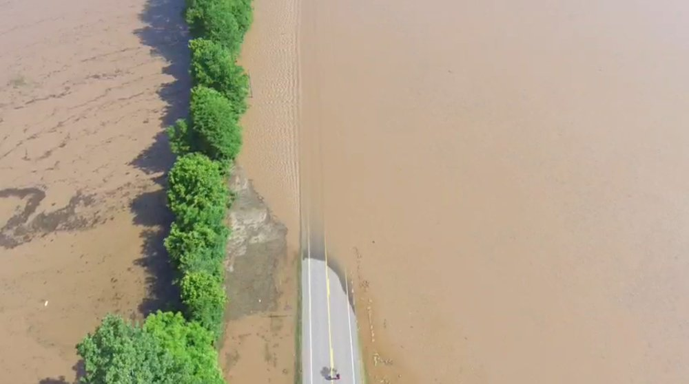 Water covers Arkansas 155 near where water tore through a levee early Friday.