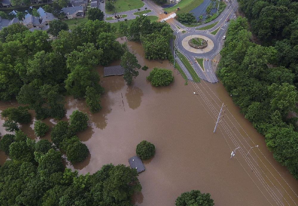 In this file photo Arkansas River floodwaters flow near the roundabout at Rebsamen Park Road and Riverfront Drive in Little Rock on Tuesday afternoon. The road is barricaded to keep out motorists for their own safety.