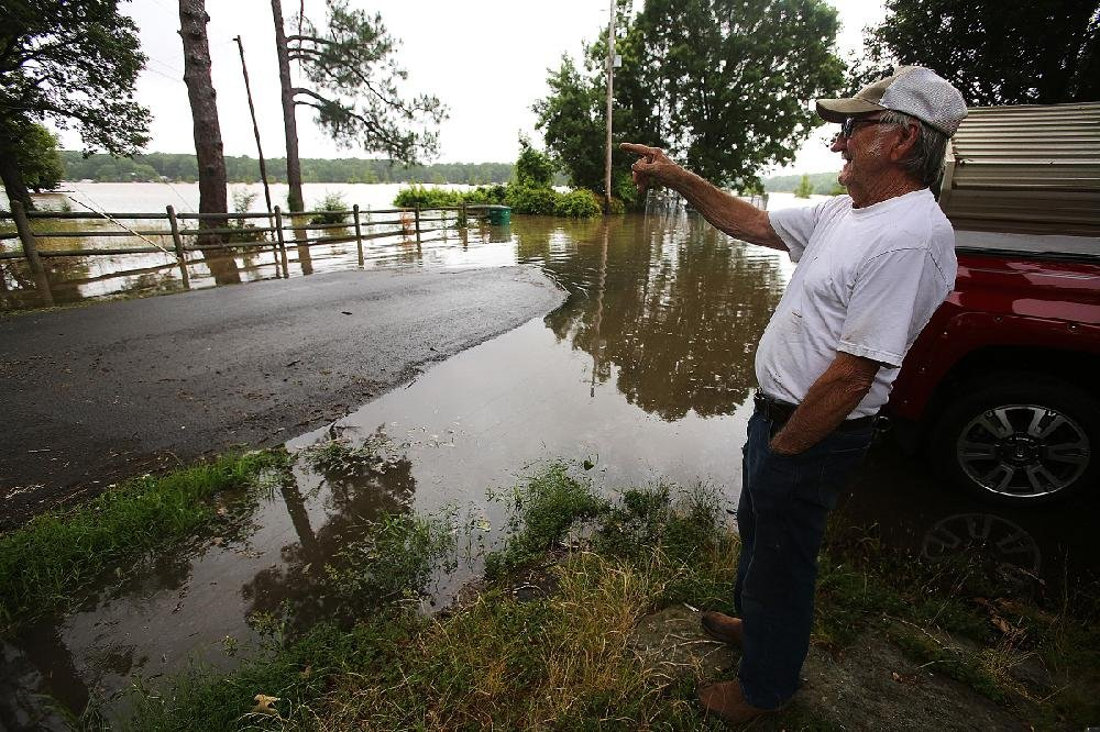 Bud Newby watches Lake Conway rise Thursday toward the backyard of his home in Mayflower. Faulkner County's County Judge Jim Baker said the lake level, already more than 4 feet above normal, was expected to rise at least another foot. More photos are available at arkansasonline.com/67flooding/