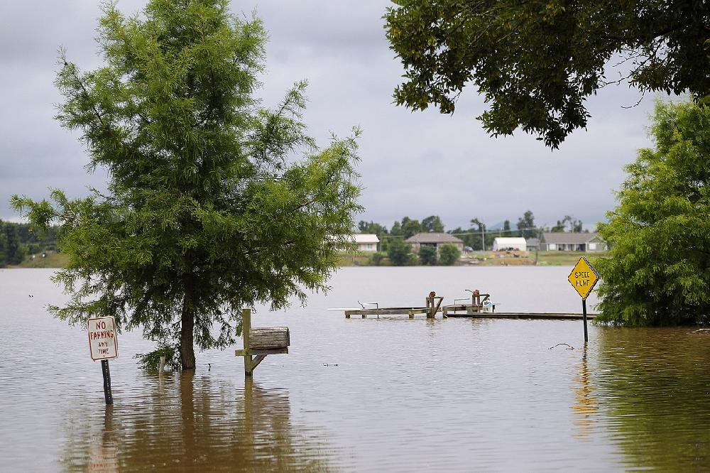 Shoreline Drive on Lake Conway is covered by floodwaters Thursday. Although the Arkansas River is starting to go down at Toad Suck, water continues to drain into the lake for now.