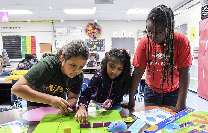 The Sentinel-Record/Grace Brown ROBOTICS: From left, Jules Claggett, 9, Cesia Gonzales, 9, and Kiarah Whittaker, 9, play a game that teaches coding during the Trojan Summer Academy and YMCA Enrichment Program at Gardner STEM Magnet School on Wednesday.