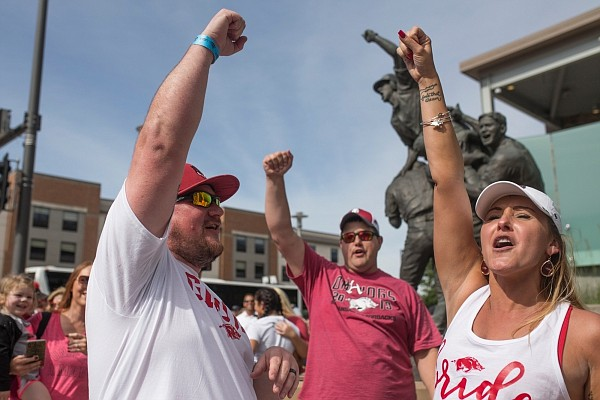 Seth Brown and Kellie Diedrich of Yukon, Okla. (from left) call the hogs after getting married during game two of the NCAA College World Series, Saturday, June 15, 2019 at the TD Ameritrade Park in Omaha, Neb.