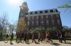 Kassandra Salazar (left), a sophomore at the University of Arkansas from Rogers, speaks Tuesday, April 5, 2016, to a group of 11th-grade students from Heritage High School in Rogers as they walk past Old Main while on a tour of the university campus in Fayetteville.