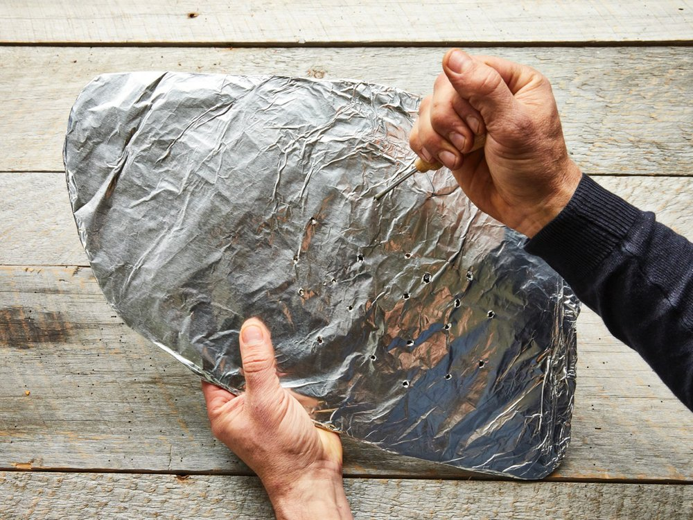 Create a platform for cooking the brisket by cutting a flat piece of cardboard the size and shape of the brisket. Cover the cut cardboard with foil and using an ice pick or a metal skewer, poke holes in it at 1-inch intervals. Photo by Tara Donne (The New York Times)