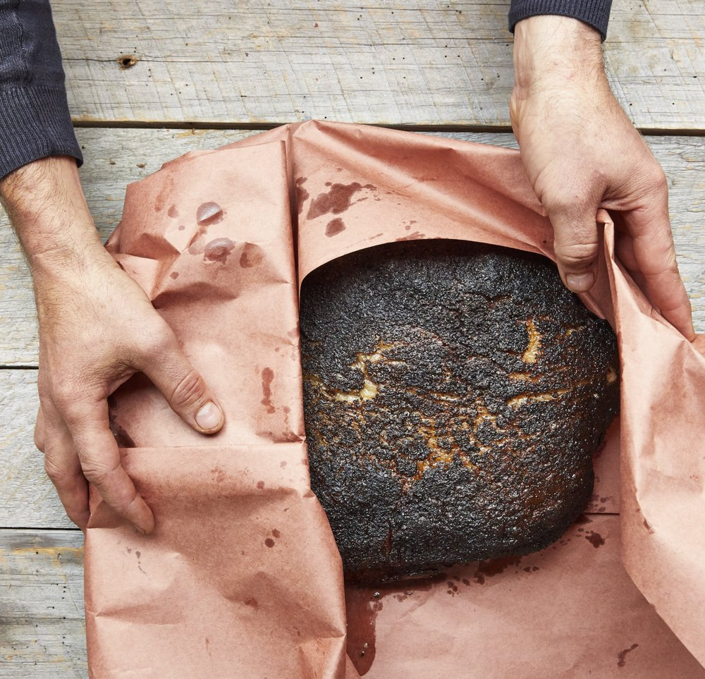 A partially cooked brisket is wrapped in pink butcher paper before going back in the smoker to finish cooking. Photo by Tara Donne (The New York Times)