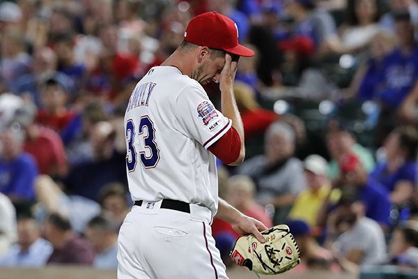 Texas Rangers' Drew Smyly wipes his face as he walks to the dugout after turning the ball over during the seventh inning of the team's baseball game against the Cleveland Indians in Arlington, Texas, Tuesday, June 18, 2019. Smyly gave up three solo home runs to the Indians in the inning. (AP Photo/Tony Gutierrez)