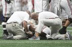 In this Dec. 1, 2018, file photo, Alabama quarterback Tua Tagovailoa (13) is helped by medical staff during the second half of the Southeastern Conference championship NCAA college football game against Georgia, in Atlanta. More than one-third of college athletic trainers say coaches influence the hiring and firing of their schools' sports-medicine staffs, a finding that counters an NCAA-recommended protocol urging medical staff to make decisions about athlete health independent of coaches and administrators. (AP Photo/John Amis, File)