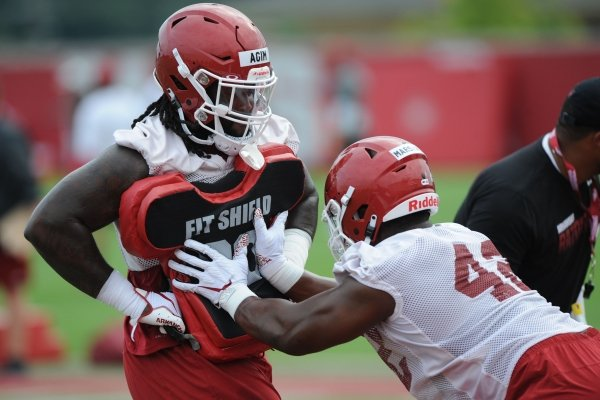 Arkansas defensive lineman McTelvin Agim (left) holds a blocking shield Friday, Aug. 2, 2019, for Jonathan Marshall during practice at the university practice field in Fayetteville. Visit nwad.com/photos to see more photographs from the practice.