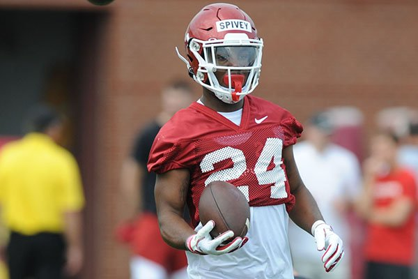 Arkansas running back A'Montae Spivey carries the ball Friday, Aug. 2, 2019, during practice at the university practice field in Fayetteville.