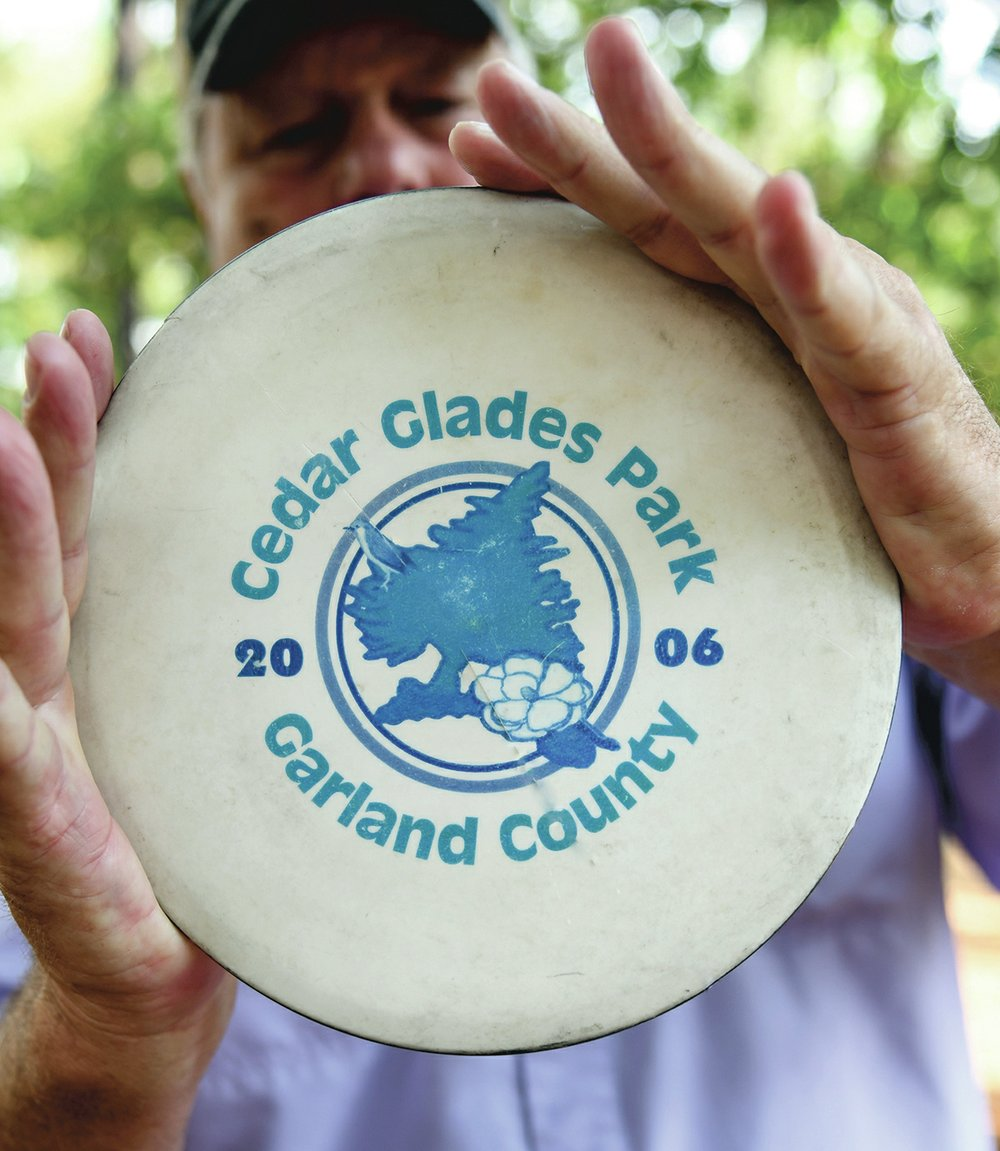 Glenn Wolf holds up a disc from the inaugural year of the Cedar Glades Park course.