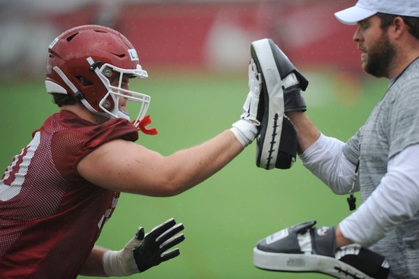 Arkansas offensive lineman Luke Jones works Saturday, Aug. 3, 2019, with assistant coach Dustin Fry during practice at the university practice field in Fayetteville. Visit nwad.com/photos to see more photographs from the practice.