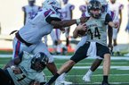 Little Rock Central quarterback Lawson Gunn (14) tries to pull away from West Memphis defensive tackle Terry Carter (left) during Tuesday night's game at War Memorial Stadium in Little Rock.  Special to the Democrat-Gazette/JIMMY JONES  See more photos at arkansasonline.com/galleries