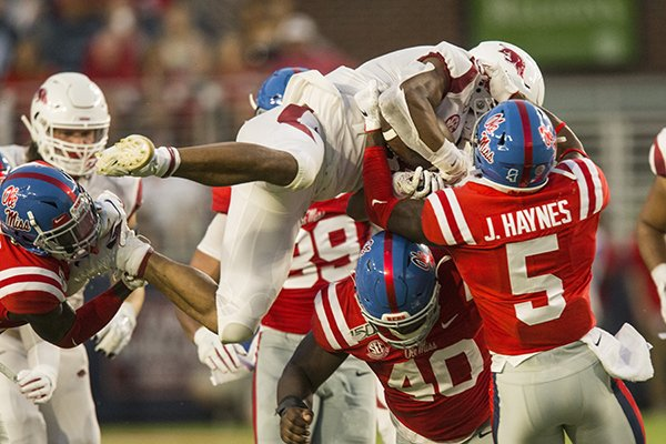 Arkansas running back Rakeem Boyd is tackled by Ole Miss defenders Josiah Coatney (40) and Jon Haynes (5) during a game Saturday, Sept. 7, 2019, in Oxford, Miss.