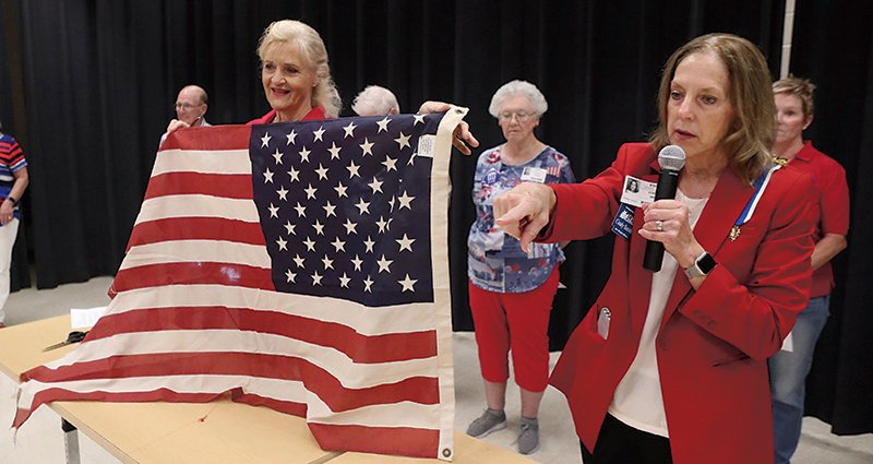 John Percifull Chapter of the Daughters of the American Revolution members Robin Williams, left, and Cindy Smith take part in a flag retirement ceremony during a Patriot Day event at the Lakeside Middle School Wednesday.  - Photo by Richard Rasmussen of The Sentinel-Record