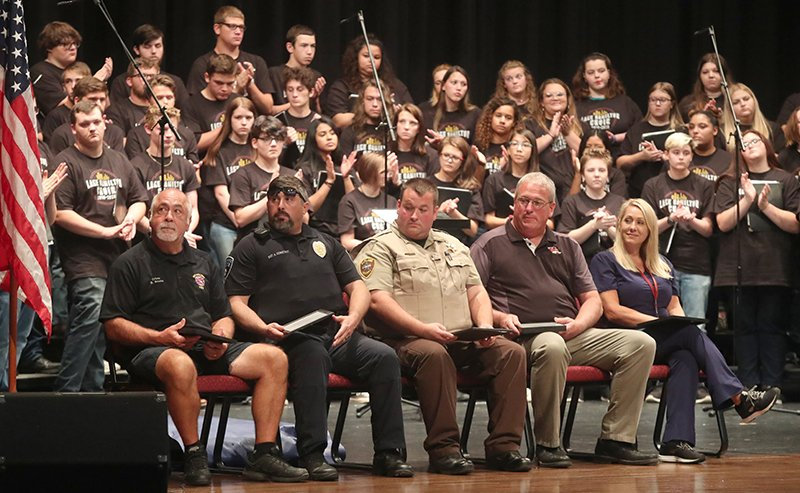 From left, Hot Springs firefighter Dean Brooks, Hot Springs police Sgt. Allen Constant, Garland County sheriff's Deputy Richard Huffman, school security representative Jeff Britt and school nurse Amy Graves sit on stage during an awards ceremony at a 9/11 remembrance ceremony at the school Wednesday. - Photo by Richard Rasmussen of The Sentinel-Record