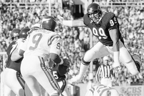 Chicago Bears tackle Dan Hampton leaps over a downed Minnesota Viking to corner quarterback Tommy Kramer during game in Chicago on Sunday, Oct. 28, 1985. The Bears won, 27-7. It was the eighth straight victory for the undefeated team. (AP Photo/Charles Bennett)