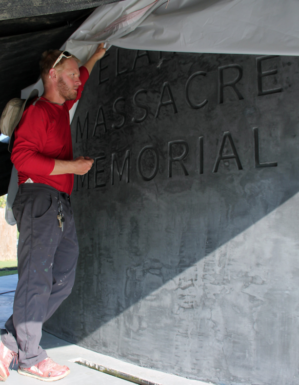 Builder and designer Amoz Eckerson shows the engraving on the south wall of the Elaine Massacre Memorial. (Arkansas Democrat-Gazette/SEAN CLANCY)