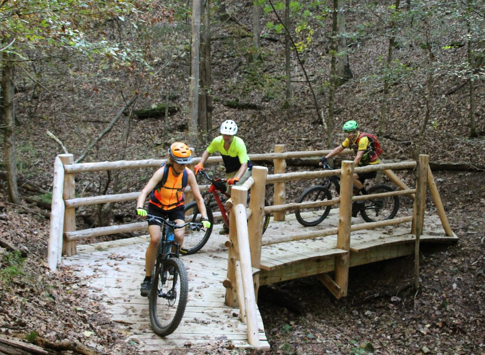 Michele Jackson, Tommy Farris, and Randy Jackson crossing a bridge Sept. 27 at Hobbs State Park-Conservation Area's Monument Trail. (Special to the Democrat-Gazette/BOB ROBINSON)