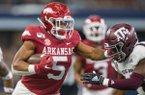 Rakeem Boyd, Arkansas running back, stiff-arms Keldrick Carper, Texas A&M safety, on a run in first quarter Saturday, Sept. 28, 2019, at AT&T Stadium in Arlington, Texas.