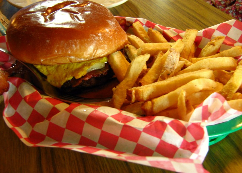 The Isaiah Montgomery burger at Magnolia Skillet in North Little Rock is topped with two kinds of cheese and a fried egg. It comes with fries tossed in your choice of seasoning. Arkansas Democrat-Gazette/Rosemary Boggs