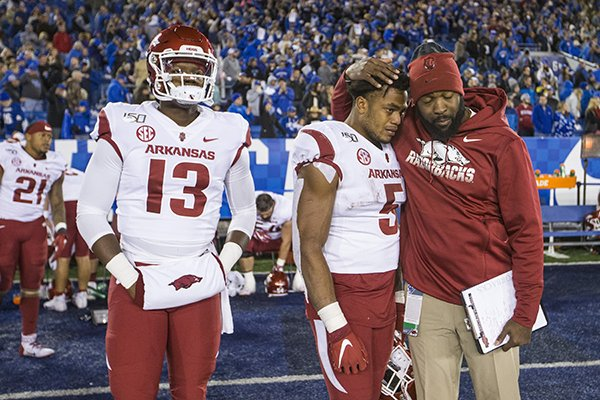 Arkansas quarterback K.J. Jefferson (13), running back Rakeem Boyd (5) and a staff member react after the Razorbacks' 24-20 loss to Kentucky on Saturday, Oct. 12, 2019, in Lexington, Ky.