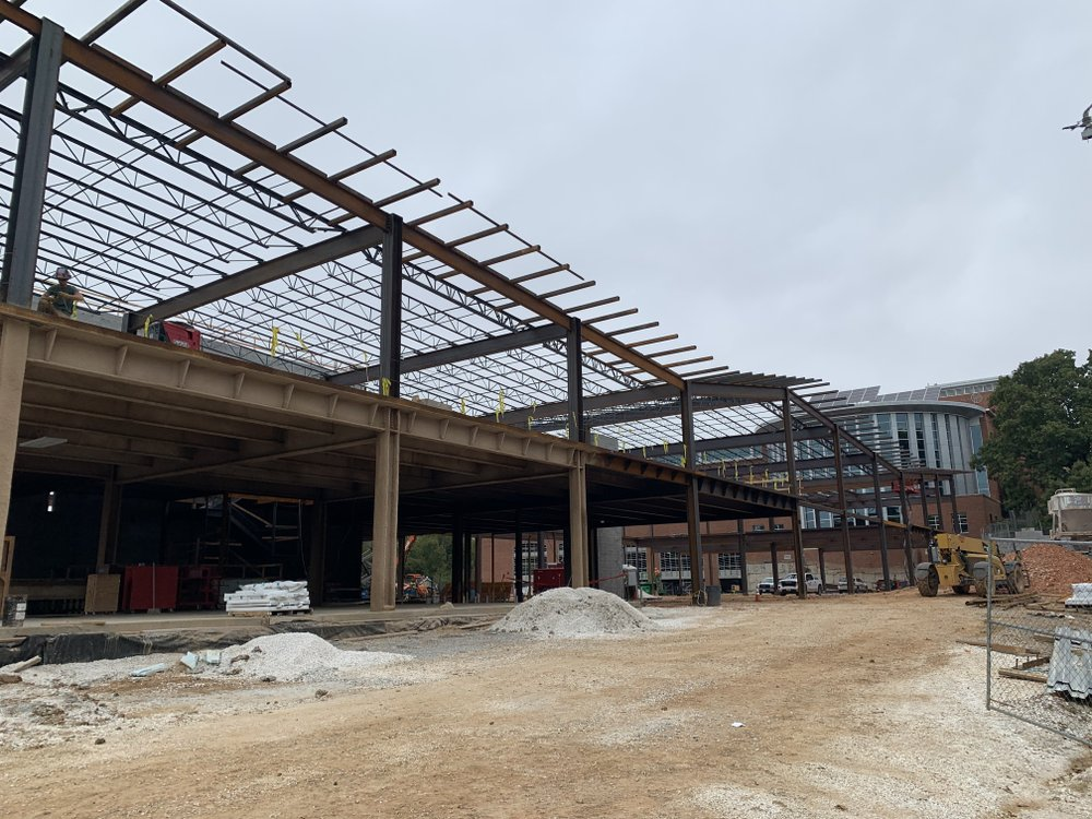Construction crews work on the expansion of the Fayetteville Public Library on Tuesday, Oct. 16, 2019. The existing library, completed in 2004, can be seen to the right behind the steel beam structures.