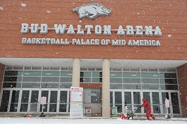 Workers clear snow from the west entrance of Bud Walton Arena on the university campus as snow falls Sunday, Feb. 2, 2014, in Fayetteville.