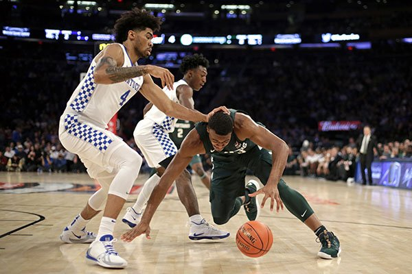 Michigan State forward Xavier Tillman (23) falls to the court in front of Kentucky forward Nick Richards (4) during the first half of an NCAA college basketball game Tuesday, Nov. 5, 2019, in New York. (AP Photo/Adam Hunger)