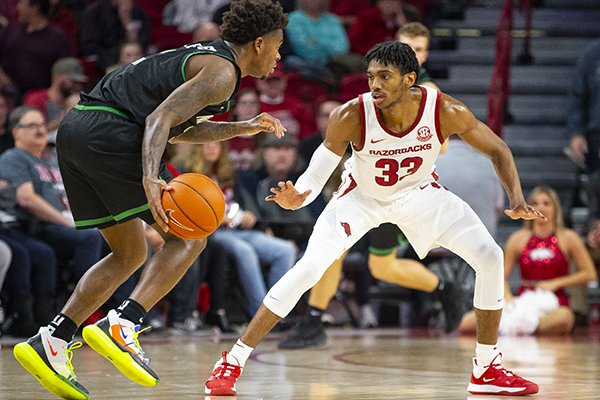 Arkansas guard Jimmy Whitt (33) defends North Texas guard Javion Hamlet (3) during a game Tuesday, Nov. 12, 2019, in Fayetteville.