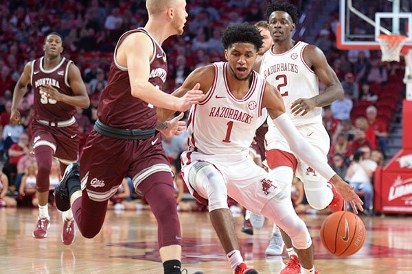 Arkansas guard Isaiah Joe (right) drives around Montana guard Timmy Falls Saturday, Nov. 16, 2019, during the second half of play in Bud Walton Arena in Fayetteville.