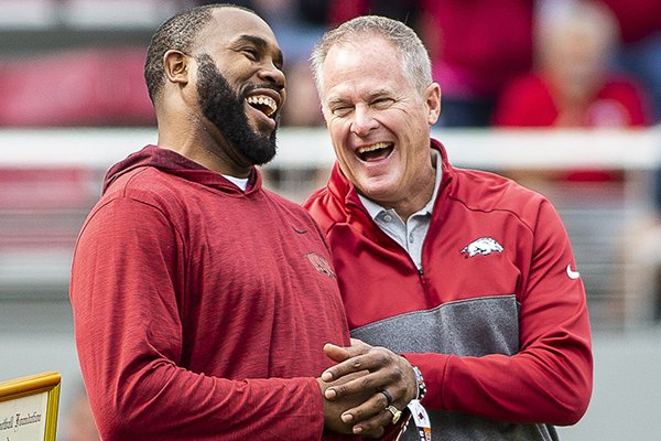 Arkansas athletics director Hunter Yurachek (right) laughs with former Arkansas running back Darren McFadden during a timeout of a game between the Razorbacks and Auburn on Saturday, Oct. 19, 2019, in Fayetteville. A federal lawsuit McFadden filed was recently dismissed without a public explanation.