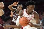 Arkansas forward Adrio Bailey (right) cuts to the basket Saturday, Nov. 16, 2019, past Montana Kendal Manuel (left) and Derrick Carter-Holilnger during the first half of play in Bud Walton Arena in Fayetteville.