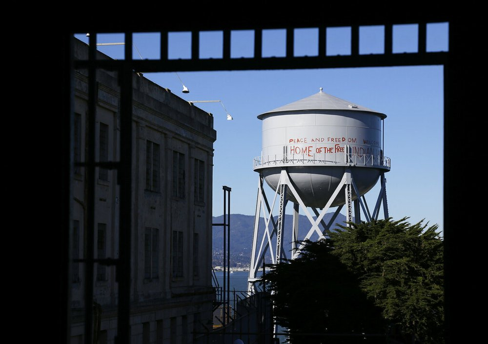 """This Jan. 14, 2013, file photo, shows a restored water tower with words that read """"Peace and Freedom Welcome Home of the Free Indian Land"""" seen through an entryway to the main cell house on Alcatraz Island in San Francisco. The words were first written on the water tower during the Native American occupation. The week of Nov. 18, 2019, marks 50 years since the beginning of a months-long Native American occupation at Alcatraz Island in the San Francisco Bay. (AP Photo/Eric Risberg, File)"""