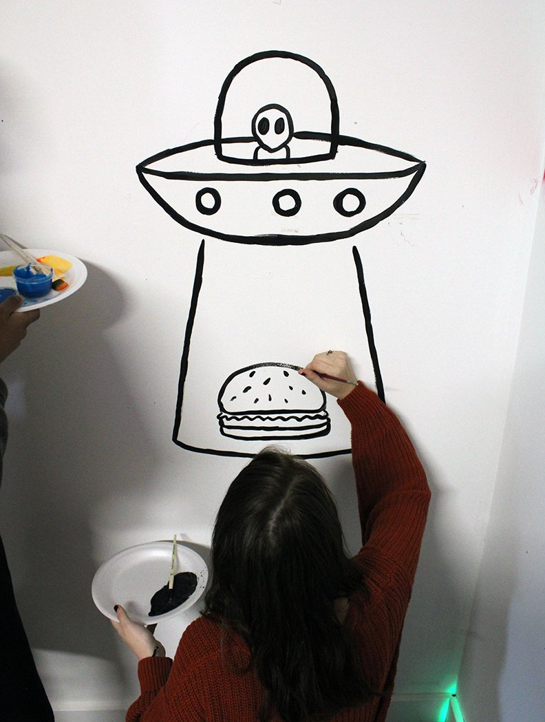 An Upward Bound student, right, paints an alien abducting a hamburger on a wall at the C4K studio. All of the various artworks painted on the walls will be used in a music video that will be shot in the studio in the near future. - Photo by Tanner Newton of The Sentinel-Record