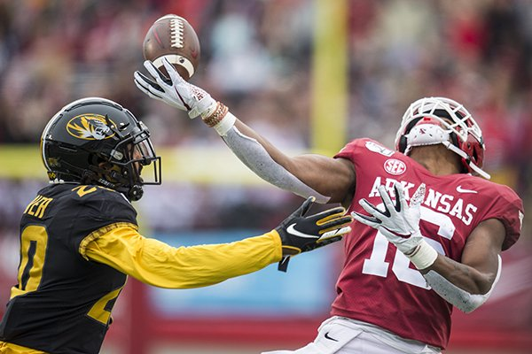 Arkansas receiver Treylon Burks tries to catch a pass while Missouri defensive back Khalil Oliver covers him during a game Friday, Nov. 29, 2019, in Little Rock.