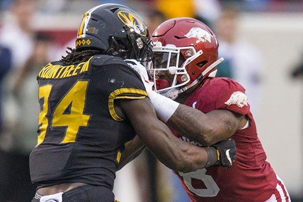 Arkansas linebacker De'Jon Harris (right) is blocked by Missouri running back Larry Rountree III during a game Friday, Nov. 29, 2019, in Little Rock.