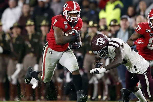 Georgia running back D'Andre Swift (7) is topped by Texas A&M linebacker Ikenna Okeke (20) in the second half of an NCAA college football game Saturday, Nov. 23, 2019, in Athens, Ga. Georgia won 19-13. (AP Photo/John Bazemore)
