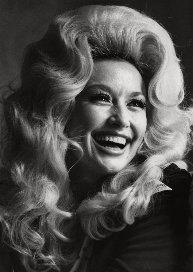 """Dolly Parton, photographed in 1975, had three No. 1 country hits in a row in 1973-74 — """"Jolene,"""" """"I Will Always Love You"""" and """"Love Is Like a Butterfly."""" Also in 1974, she and Porter Wagoner reached No. 1 with """"Please Don't Stop Loving Me."""" Parton continued her No. 1 run in 1975 with """"The Bargain Store."""" Two years later, she had her first crossover hits with """"Light of a Clear Blue Morning"""" and """"Here You Come Again."""" (The New York Times/JACK MANNING)"""