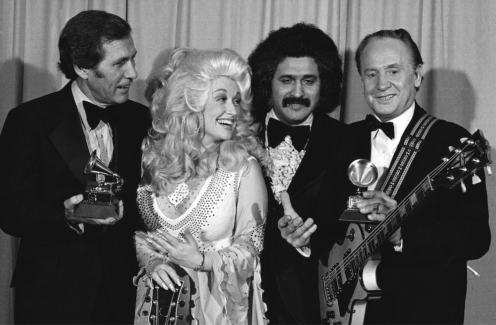 Chet Atkins (left) and Les Paul (right) received Grammy Awards in 1977 from Dolly Parton and Freddie Fender, who were presenters on the broadcast. (AP)