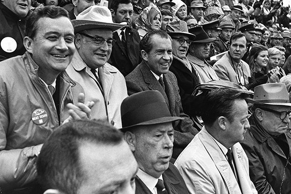 """President Richard M. Nixon, second row, second from left, watches """"The Big Shootout"""" football game between Arkansas and Texas in the stands at Razorback Stadium in Fayetteville, Ark., in this December 6, 1969 file photo. Seated beside Nixon from left are Rep. John Paul Hammerschmidt, R-Ark., Ark. Gov. Winthrop Rockefeller, Sen. John L. McClellan, D-Ark., Sen. J. William Fulbright, D-Ark., Rep. George H. Bush, R-Tex., and on the first row, left, University of Arkansas President David W. Mullins. Then ranked No. 1 Texas won the game and the national championship by defeating No. 2 Arkansas 15-14. (AP Photo/White House via Special Collections, University of Arkansas Libraries, Fayetteville, File)"""