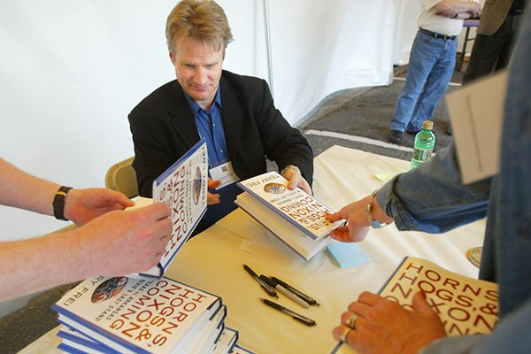 Terry Frei signs stacks of his book Horns, Hogs and Nixon Coming during the Arkansas Literary Festival Saturday afternoon in the Rivermarket.