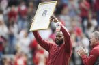 Former Arkansas running back Darren McFadden holds up a plaque commemorating his election to the College Football Hall of Fame during a football game between the Razorbacks and Auburn on Saturday, Oct. 19, 2019, in Fayetteville.