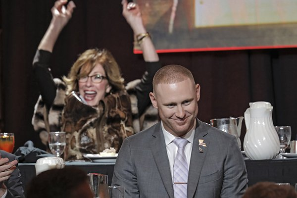 LSU passing game coordinator Joe Brady smiles after winning the 2019 Broyles Award on Tuesday, Dec. 10, 2019, in Little Rock. In the background Carole Smith reacts as his name is announced. Smith hosted Brady and his girlfriend during their state in Little Rock. The Broyles Award is given to the top college assistant coach in the country.