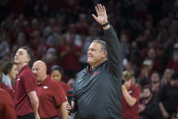 Arkansas football head coach Sam Pittman greets fans Saturday during a timeout in the basketball game at Walton Arena in Fayetteville. Pittman has a tough recruiting job ahead with the early signing period, which starts today and runs through Friday. - Photo by Ben Goff of the NWA Democrat-Gazette