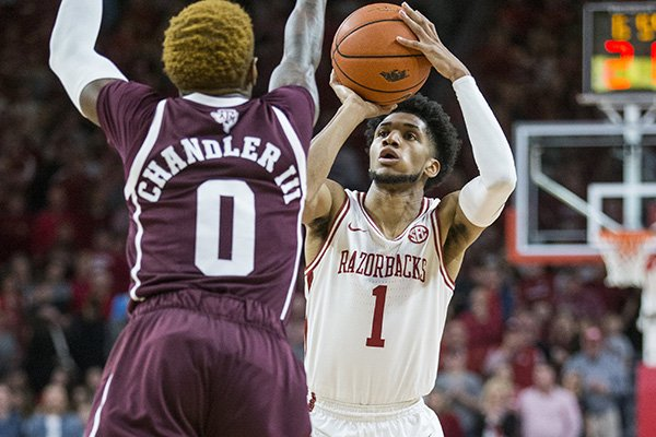 Arkansas guard Isaiah Joe (1) shoots against Texas A&M defender Jay Jay Chandler during a game Saturday, Jan. 4, 2020, in Fayetteville.