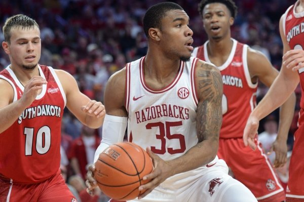 Arkansas forward Reggie Chaney (35) looks to pass out of the lane Friday, Nov. 22, 2019, as he is pressured by South Dakota guard Cody Kelley (10) and forward Tyler Hagedorn (right) during the second half of play in Bud Walton Arena in Fayetteville.