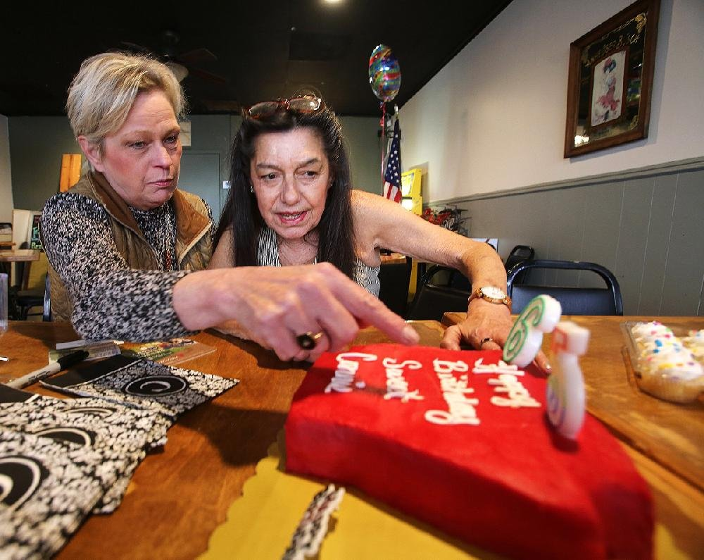 """""""Sweet Sweet"""" Connie Lee Hamzy (right) looks at her birthday cake with her friend Patricia Davis on Thursday, Jan. 9, 2019, at Grady's Pizza and Subs in Little Rock. Hamzy, the well-known groupie who was mentioned in the lyrics of Grand Funk Railroad's song """"We're an American Band,"""" turned 65 on Thursday.  (Arkansas Democrat-Gazette/Thomas Metthe)"""