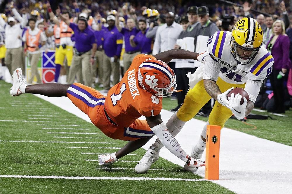 LSU tight end Thaddeus Moss scores past Clemson cornerback Derion Kendrick during the second half of Monday's College Football Playoff championship in New Orleans. Moss scored twice as LSU won 42-25.