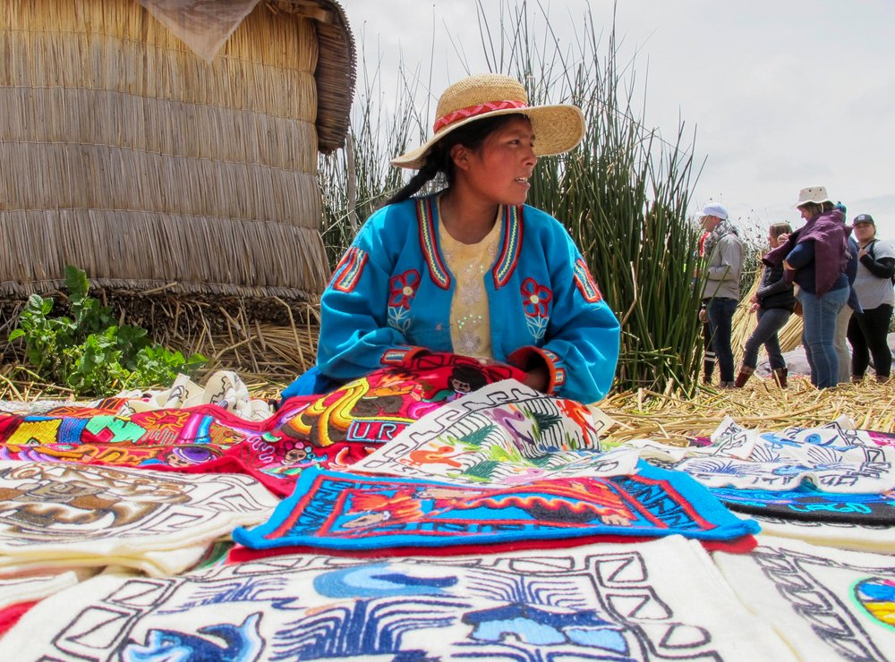 A young resident of a floating island on Lake Titicaca, an hour by boat from Puno, shares her work with visitors who have come to learn more about the traditional and modern ways of life on the island. (TNS/Thomas Curwen)